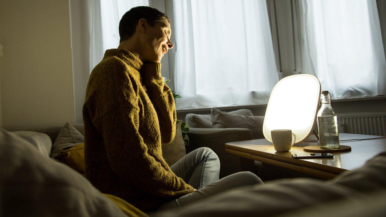 Eine Frau sitzt vor einer Tageslichtlampe. Das Entscheidende bei der Tageslichtlampe ist der hohe Blauanteil im Licht. (Foto: picture-alliance / Reportdienste, picture alliance / dpa-tmn | Christin Klose)