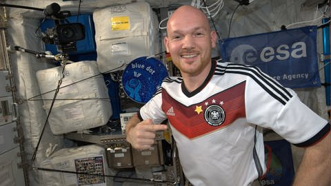 Alexander Gerst im Juli 2014 mit einem T-Shirt der deutschen Fußballnationamannschaft – ergänzt um einen 4. Stern nach der gewonnenen Weltmeisterschaft  (Foto: picture-alliance / Reportdienste, picture alliance / AP Photo | Uncredited)