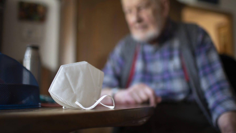 Senior, auf dem Tisch eine FFP2-Maske: Bei geimpften Personen ist die Gefahr, dass die andere Menschen mit dem Coronavirus infizieren können, deutlich reduziert (Foto: Imago, IMAGO / photothek)