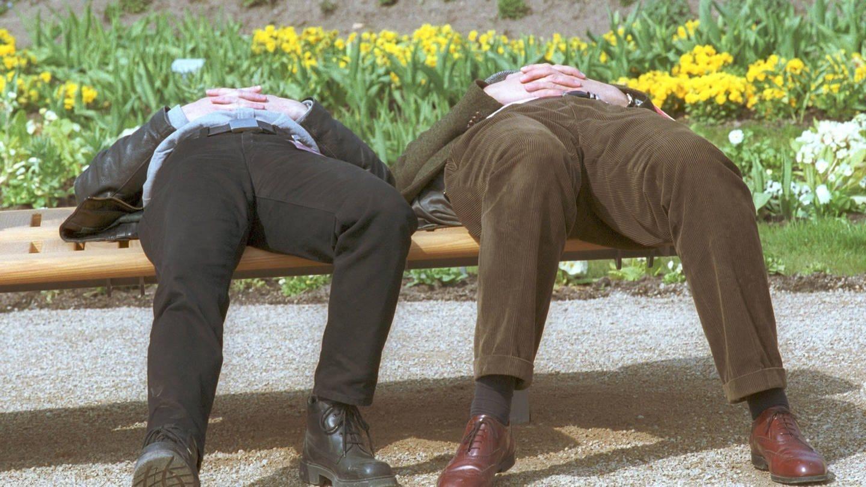 Frühjahrsmüde: Zwei Männer schlafen, umringt von Frühlingsblumen, auf einer Parkbank (Foto: Imago, IMAGO / photothek)