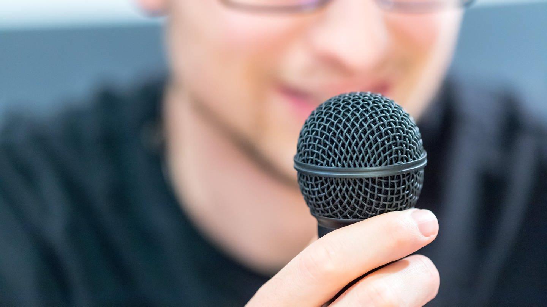 Junger Mann hält Mikrofon vor dem Gesicht: Wenn man in ein Mikrofon spricht, kommt beim Mikrofon der Schall nur über die Luftleitung an – nicht über die Knochenleitung. Deshalb klingt es so anders.