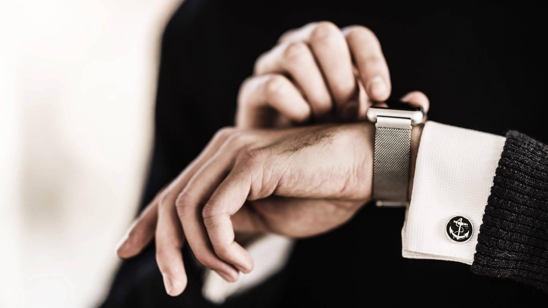 Mann schaut auf Uhr