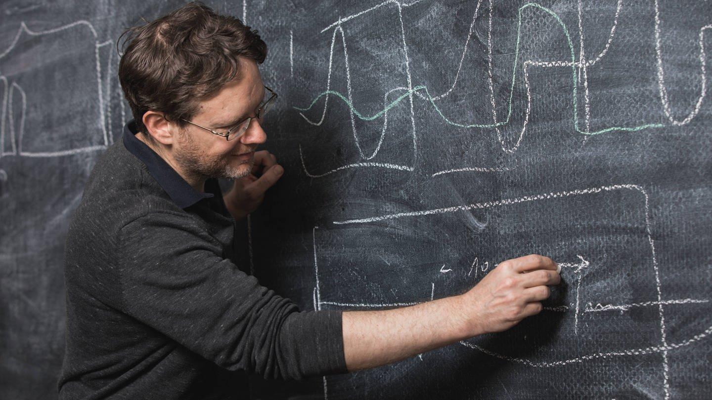 Mann schreibt an Tafel (Foto: Imago, imago images / Viviane Wild)
