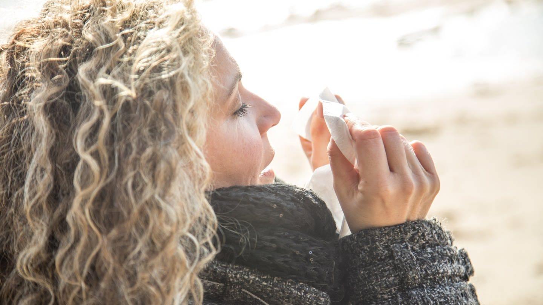 Frau beim Winterspaziergang putzt sich die Nase (Foto: picture-alliance / Reportdienste, picture alliance / dpa Themendienst)