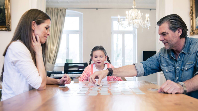 Kind und Eltern spielen gemeisam Memory: Ist Konzentrationsfähigkeit angeboren? (Foto: Imago, imago/Westend61)