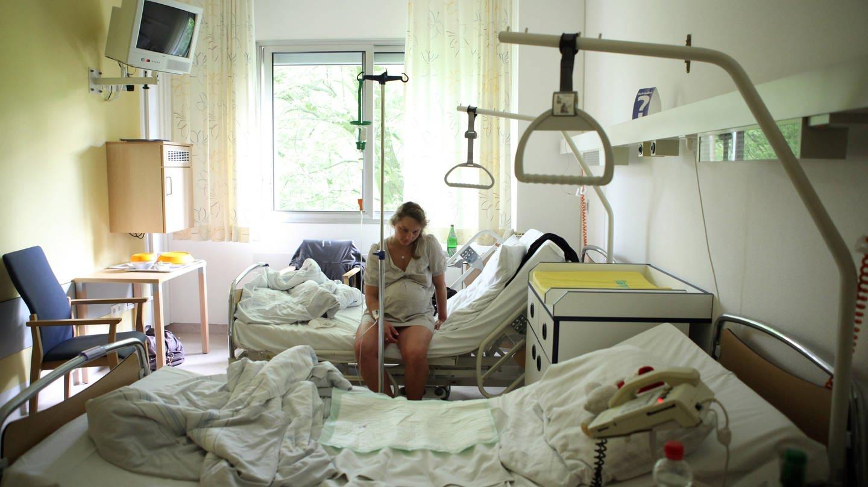 Schwangere mit Schmerzen sitzt allein auf einem Krankenhausbett (Foto: Imago, imago stock&people)