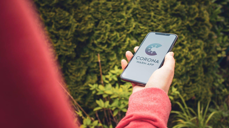 Jemand hält ein Smartphone mit der geöffneten Corona-Warn-App (Foto: Imago, imago images / Mario Aurich)
