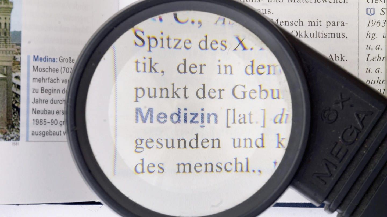 Eintrag Medizin im Lexikon unter Lupe (Foto: picture-alliance / Reportdienste, imageBROKER)