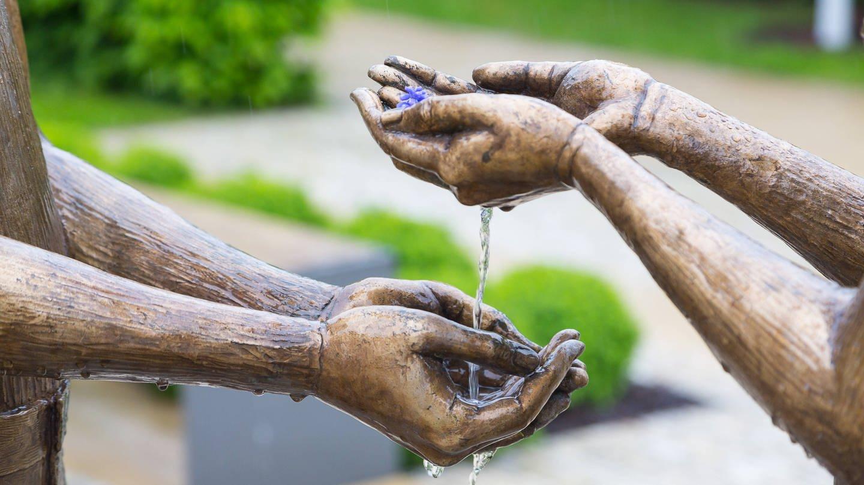 Hände zweier Bronzefiguren, die sich das Wasser reichen, in Radebeul, Sachsen