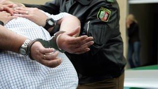Gewalttätiger Ehemann wird von Polizei in Handschellen abgeführt (Foto: Imago, imago/Sven Simon)