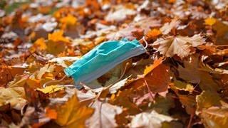 Corona-Pandemie - eine Einweg-Maske liegt im Herbstlaub. (Symbolfoto) (Foto: Imago, imago images/MiS)