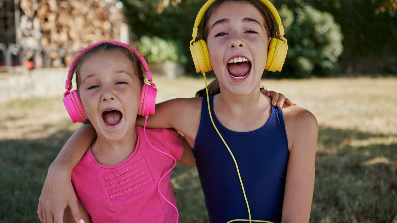 Zwei Mädchen mit Kopfhörern singen mit weit geöffneten Mündern