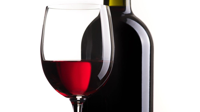 Rotweinglas und Flasche vor weißem Hintergrund (Foto: Imago, stokkete via www.imago-images.de)