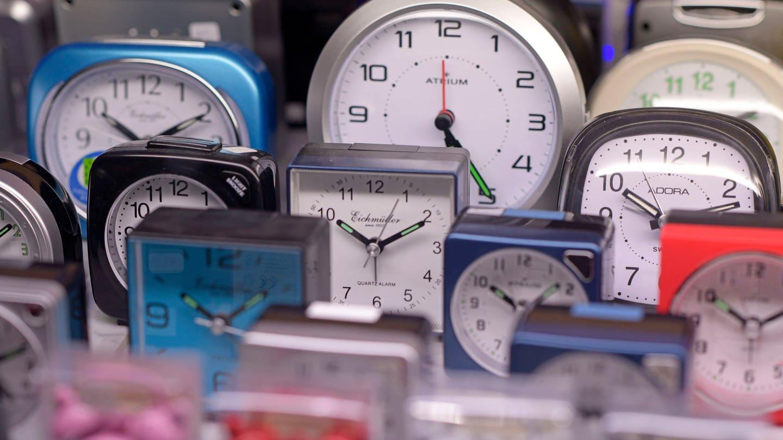 In der Auslage eines Uhrengeschäftes stehen unzählige Wecker