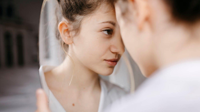 Eine junge Person schaut ganz nah in einen Spiegel (Foto: Imago, Tania Cervian via www.imago-images.de)