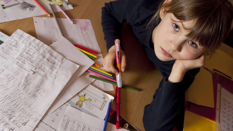 Kind schaut traurig vom Hausaufgabenmachen auf (Foto: Imago, imago/blickwinkel)