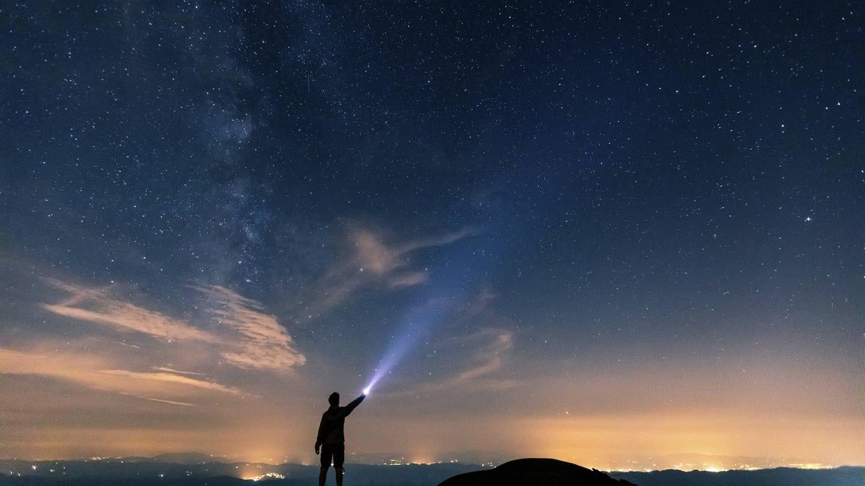 Ein Mensch leuchtet mit einer Taschenlampe gen Sternenhimmel (Foto: Imago, William Perugini via www.imago-images.de)