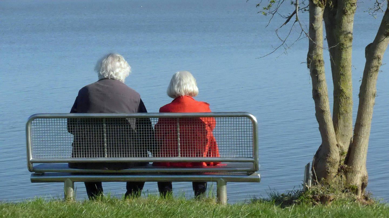 Ein Seniorenehepaar sitzt auf einer Bank am See und schaut aufs Wasser. (Foto: Imago, IMAGO / Eckhard Stengel)