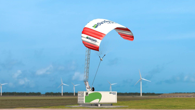 Ein rot-weißer Lenkdrachen schwebt über einem grün-weißen Container, der auf einer großen Wiese steht. (Foto: Pressestelle, Skysails Power GmbH)