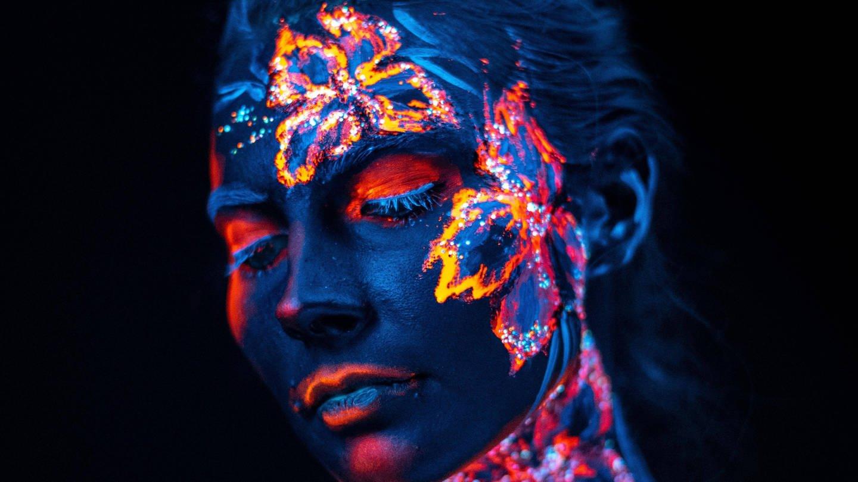 Bemaltes Gesicht einer Frau in UV-Licht (Foto: Imago, IMAGO / Panthermedia)
