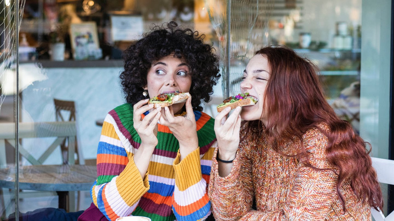 Zwei Frauen beißen beim Frühstück herzhaft in belegte Brote.