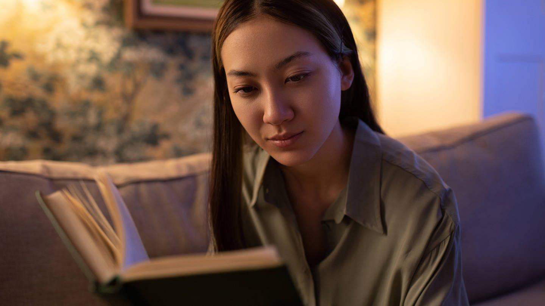 Frau beim Lesen: Bringt es etwas, abends zu lernen bzw. vor dem Schlafengehen zu wiederholen? (Foto: Imago, IMAGO / Cavan Images)