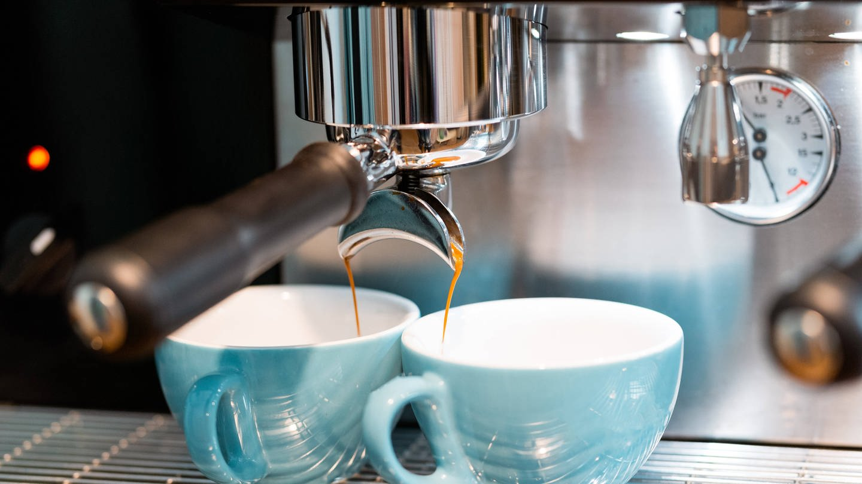 Zwei blaue Tassen unter Espressomaschine: Warum schmeckt Espresso anders als Filterkaffee? (Foto: Imago, IMAGO / Addictive Stock)