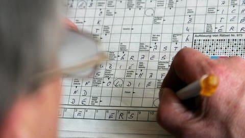 A man fills out a crossword puzzle (symbol picture).  (Photo: dpa Bildfunk, picture alliance / dpa | Gero Breloer (symbol image))