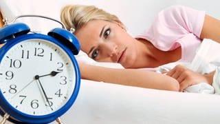 Eine frau liegt nachts im Bett und starrt auf den Wecker. (Foto: Imago, IMAGO / blickwinkel)