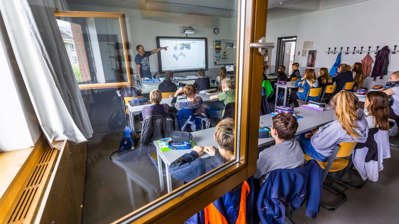Schüler*innen sitzen in einem Klassenzimmer bei geöffnetem Fenster