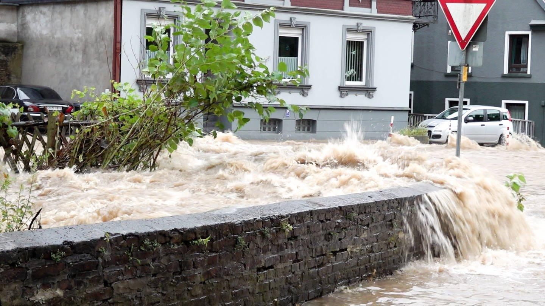 Wasserfluten in Fluten von Altena, Nordrhein-Westfalen. Werden Wetterextreme, wie Hochwasser oder Hitzeperioden in Zukunft zunehmen?