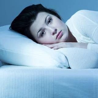 Eine Frau liegt wach im Bett. (Foto: Getty Images, Thinkstock -)