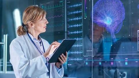 Eine Ärztin begutachtet ein Nervensystem an einem großen Bildschirm. (Foto: Getty Images, Getty Images - gorodenkoff)