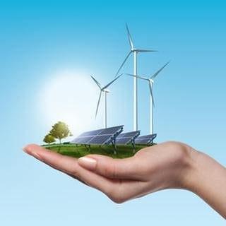 In einer Frauenhand befindet sich eine Wiese mit einer Photovoltaikanlage und Windrädern, im Hintergrund ist ein blauer Himmel zu sehen. (Foto: Getty Images, Thinkstock -)