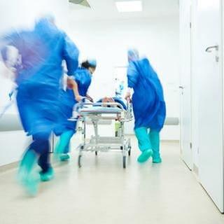 Ein Krankenbett wird durch einen Krankenhausflur rennend geschoben. Ärzte eilen herbei. (Foto: Getty Images, Thinkstock -)