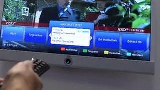 Eine Frau schaut sich verschiedene Optionen auf einem Smart TV an. (Foto: picture-alliance / dpa, picture-alliance / dpa -)