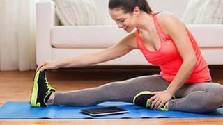 Eine Frau trainiert mit einer Fitness-App (Tablet) (Foto: Colourbox, Model Foto: Colourbox.de -)