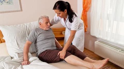 Pflegerin hilft altem Mann aus dem Bett (Foto: Colourbox, Foto: Colourbox.de -)