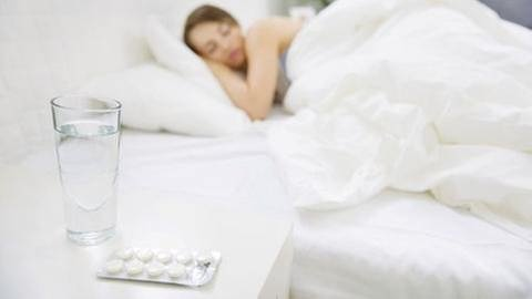 Eine Frau schläft im Vordergrund liegen Schlaftabletten (Foto: Getty Images, Thinkstock -)