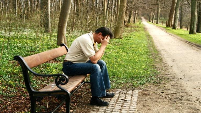 Ein Mann sitzt auf einer Parkbank und stützt seinen Kopf in die Hände. Um ihn herum befindet sich eine blühende Frühlingslandschaft. (Foto: Colourbox, Model Foto: Colourbox.de -)
