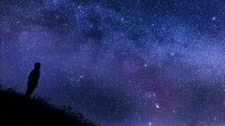 Ein Mann steht auf einem Berg und betrachtet die Sterne. (Foto: Getty Images, Thinkstock -)