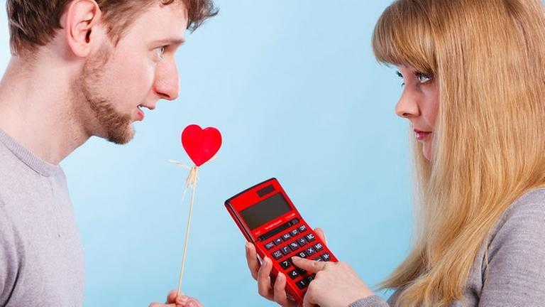 Ein Mann und eine Frau sthen sich gegenüber, er hält ein Herz, sie einen Taschenrechner. (Foto: Getty Images, Thinkstock -)