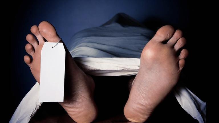 Ein toter Mensch ist in einer Leichenhalle aufgebahrt. Die nackten Füße schauen aus dem Leichentuch hinaus. (Foto: Getty Images, Thinkstock -)