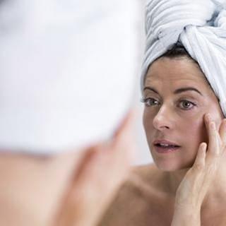 Eine Frau betrachtet ihre Haut im Badezimmerspiegel. (Foto: Getty Images, Thinkstock -)
