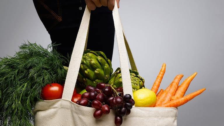 Eine Frau trägt eine Einkaufstasche mit Lebensmittel (Foto: Getty Images, Thinkstock -)