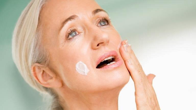 Eine ältere Frau cremt sich ihr Gesicht ein (Foto: Getty Images, Thinkstock -)