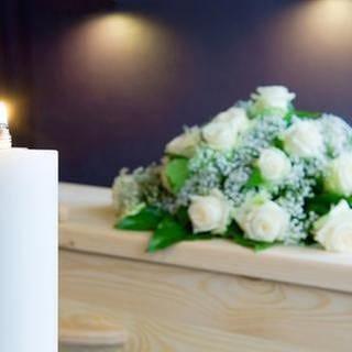 Eine brennende Kerze steht neben einem Sarg mit Blumenschmuck. (Foto: Getty Images, Thinkstock -)