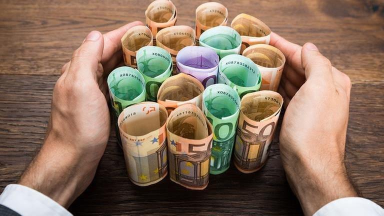 Hände umfassen einige Gelscheine auf einem Tisch. (Foto: Getty Images, Thinkstock -)