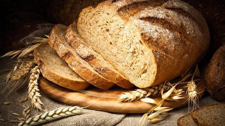Weizenähren und aufgeschnittenes Weizenbrot liegen auf einem Tisch (Foto: Getty Images, Thinkstock -)