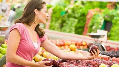 Eine Frau beim Einkaufen, sie hält einen roten Apfel in der Hand und begutachtet ihn. (Foto: Colourbox, Model Foto: Colourbox.de -)